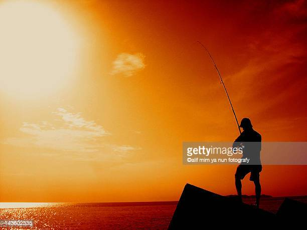 man fishing at sunset - nun stock-fotos und bilder
