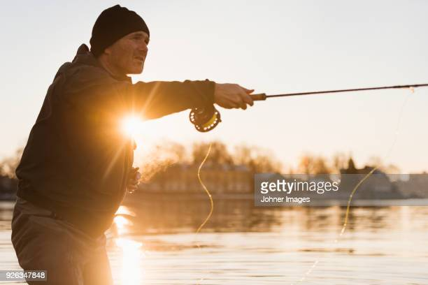 man fishing at sunset - hobbies stock pictures, royalty-free photos & images