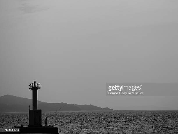 Man Fishing By Lighthouse Against Clear Sky