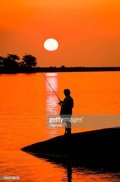 homem pesca ao pôr do sol - ogphoto imagens e fotografias de stock