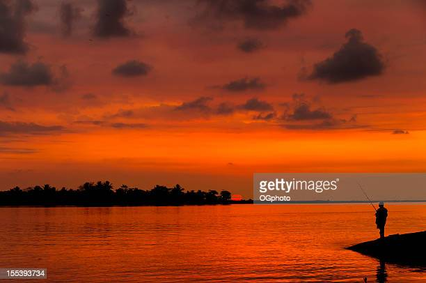 man fishing during sunset - ogphoto stock photos and pictures