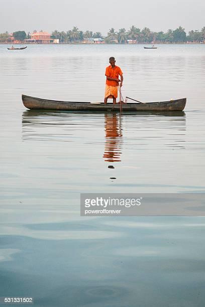 Man fishing from a Kettuvallam on Vembanad Lake, Kumarakom, India