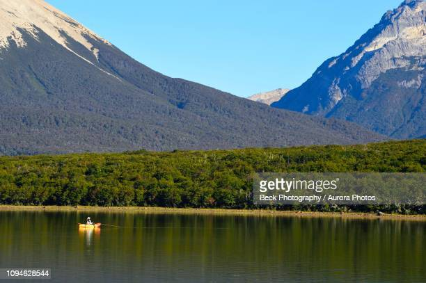 man fishing from kayak at tres valles lake, argentina - três pessoas stock pictures, royalty-free photos & images