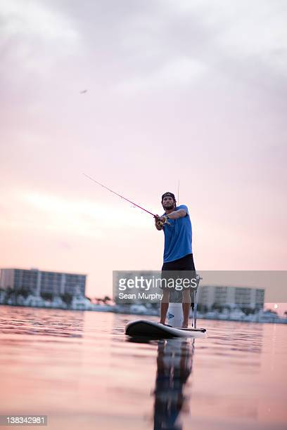 man fishing from paddle board - paddleboard stock photos and pictures