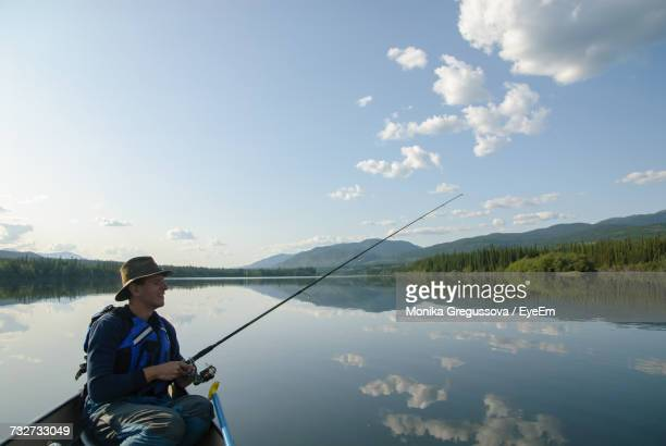 man fishing in lake while sitting in boat against sky - monika gregussova stock pictures, royalty-free photos & images