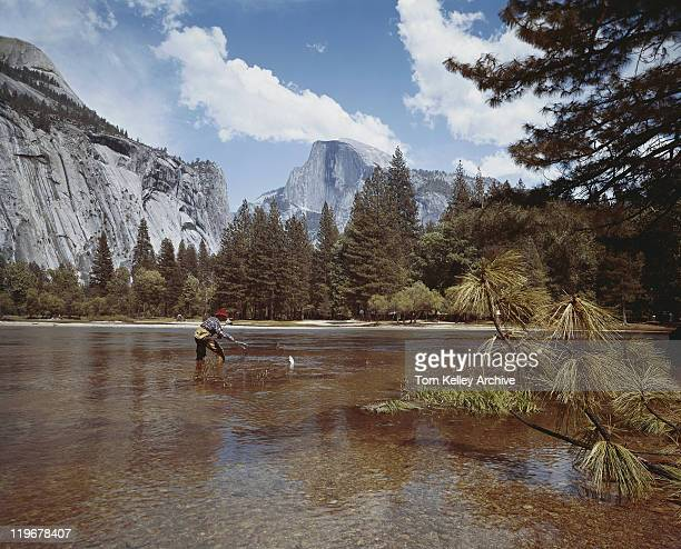 man fishing in lake with mountains in background - 1960 stock pictures, royalty-free photos & images