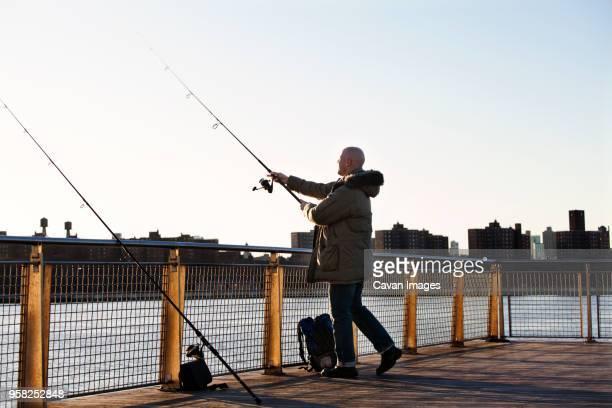 man fishing in river against clear sky - careca imagens e fotografias de stock