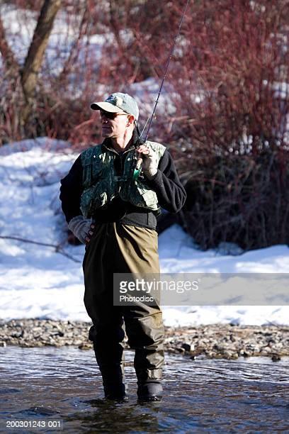 man fishing in river, in winter - wasserform stock-fotos und bilder