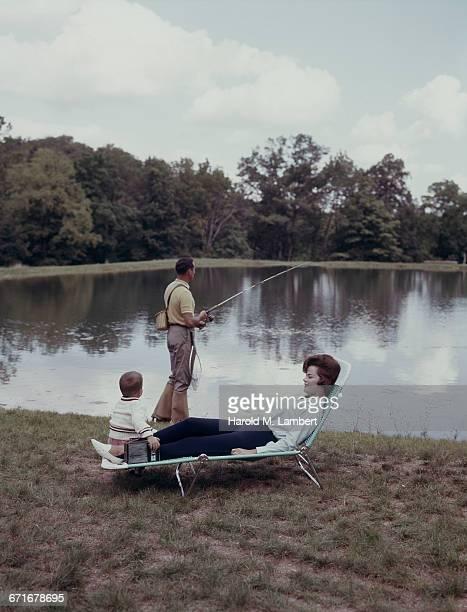 man fishing in river while mother and son sitting besides  - {{relatedsearchurl(carousel.phrase)}} imagens e fotografias de stock
