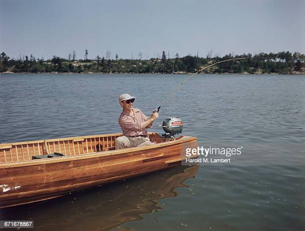 man fishing in river while sitting in motorboat  - number of people stock pictures, royalty-free photos & images