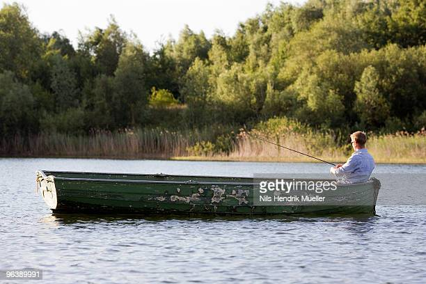 man fishing in rowboat - rowing boat stock pictures, royalty-free photos & images