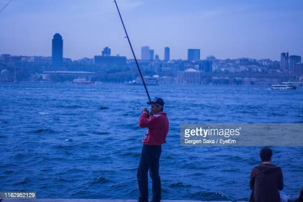 man fishing in sea against cityscape - saka stock pictures, royalty-free photos & images