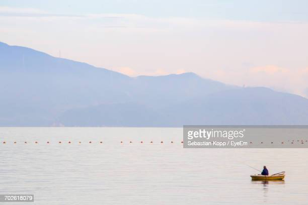 Man Fishing In Sea While Sitting On Boat Against Sky
