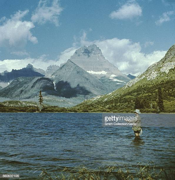 Man fishing in Swiftcurrent Lake Glacier National Park Montana 1966
