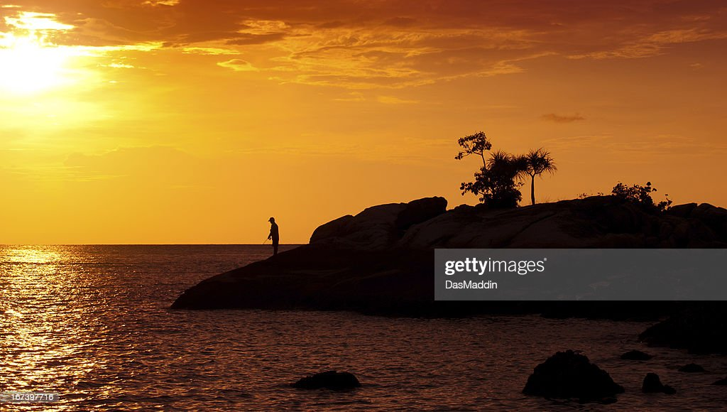Man fishing in the sunset : Stock Photo