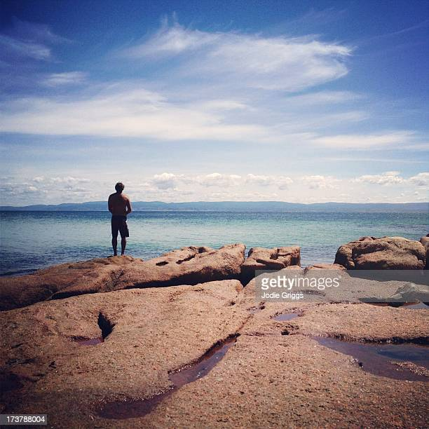 Man fishing off rocks into the ocean on hot day
