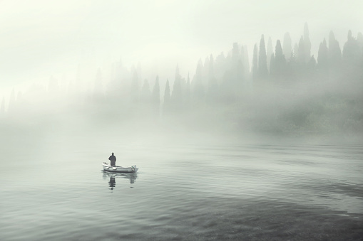 Man fishing on a boat in a mistic foggy lake 866955294