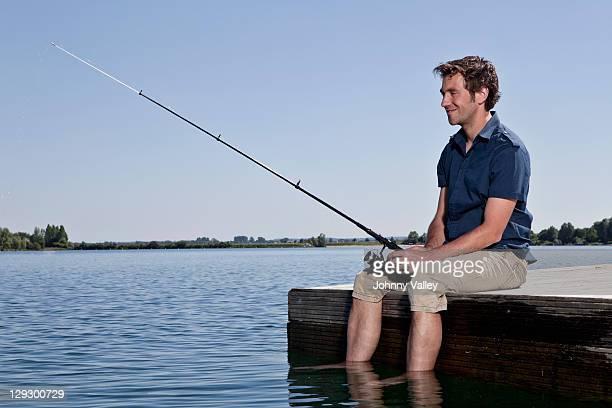 man fishing on dock - angeln stock-fotos und bilder