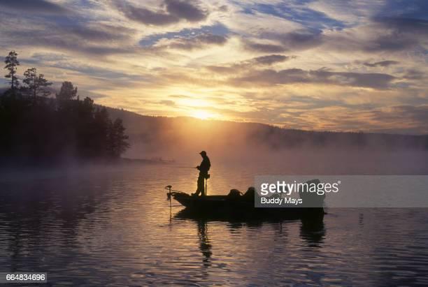 man fishing on mountain lake - largemouth bass stock pictures, royalty-free photos & images