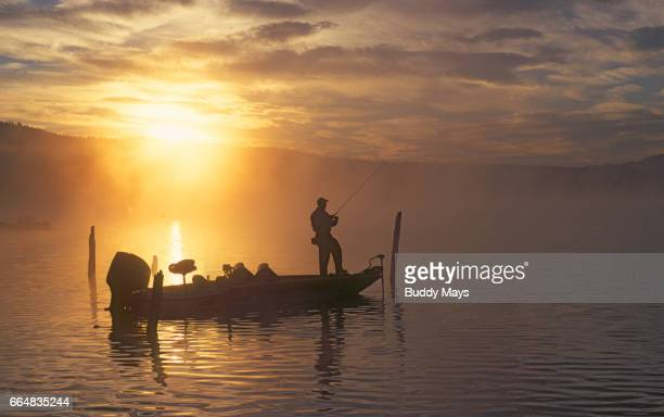 man fishing on mountain lake - big game fishing stock photos and pictures