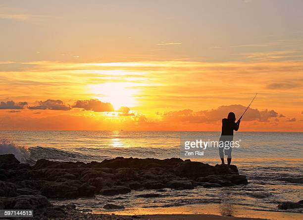 Man fishing on rocky shoreline at sunrise