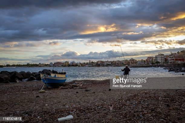 man fishing on the beach of girdini naxos, fishingboat on the beach - finn bjurvoll stock pictures, royalty-free photos & images