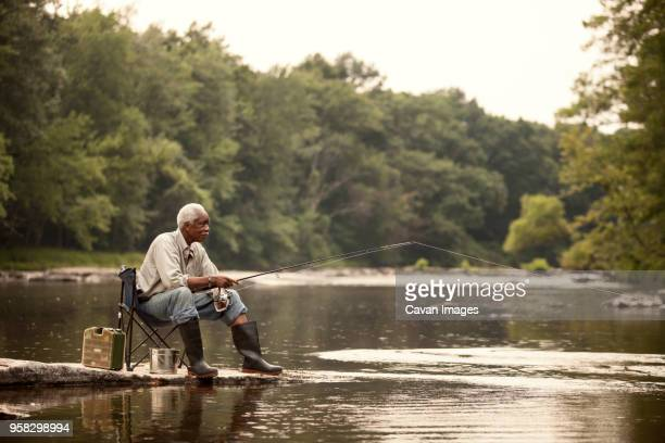 man fishing while sitting on chair at lake - fishing stock pictures, royalty-free photos & images