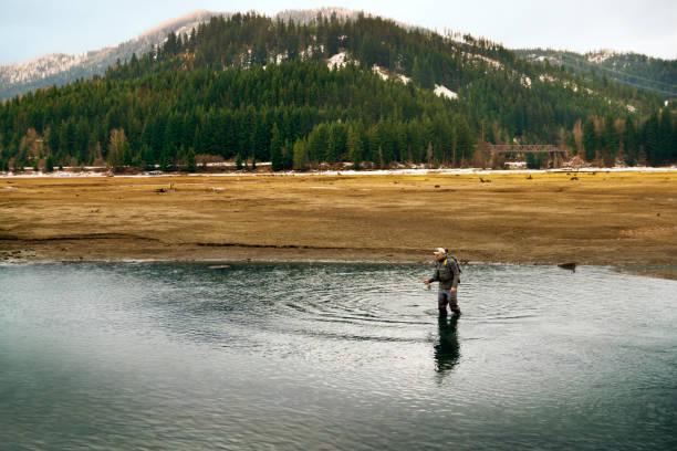 Man fishing while standing in lake