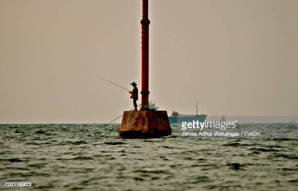 Man Fishing While Standing On Metal Structure Amidst Sea