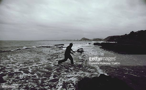 Man Fishing With Net At Sea Shore Against Cloudy Sky