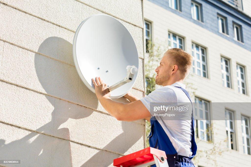 Mann passende TV-Satellitenschüssel : Stock-Foto