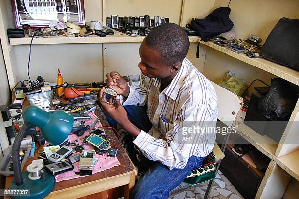 Man fixes a cellular telephone on June 22, 2009 in Ouagadougou. Sales of cellular telephones in Burkina Faso have been multiplied by 100 over the...