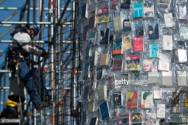 A man fixes books wrapped into plastic bags on a scaffolding as part of the documenta art work The Parthenon of Books by Argentinean artist Marta...