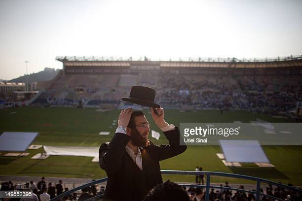 A man fixes his hat on his head as tens of thousands of Ultra Orthodox Jews attend Siyum HaShas a celebration marking completion of a sevenand a half...