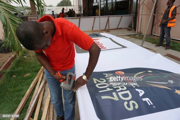 A man fixes on a plank a banner of the Confederation of African Football outside the International Conference Centre on the eve of the CAF awards...