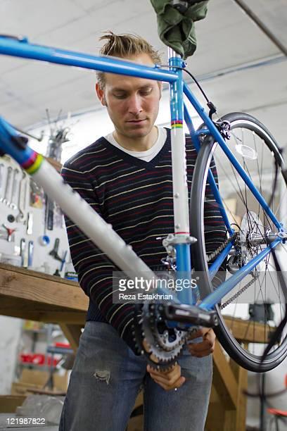 Man fixes pedal on bike under repair