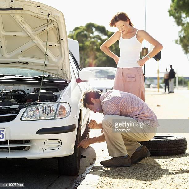 man fixing a car tire and woman standing watching - partire bildbanksfoton och bilder