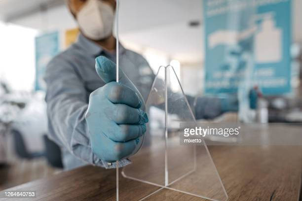 man fixing acrylic glass at office counter - infectious disease stock pictures, royalty-free photos & images