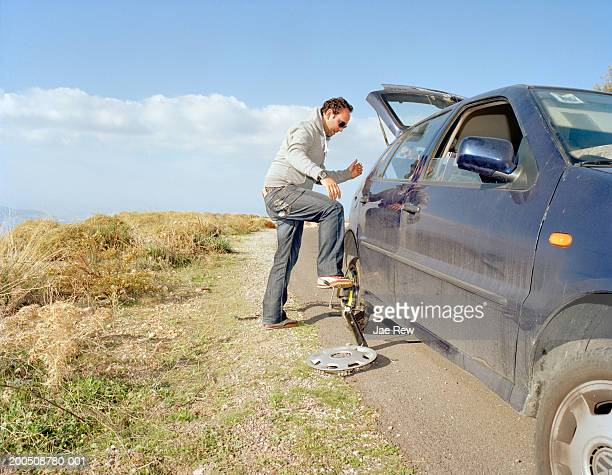 Man fixing flat tire