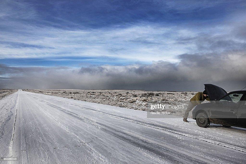 Man fixing his car on remote winter road : Bildbanksbilder
