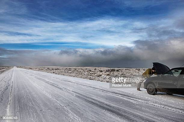 Man fixing his car on remote winter road