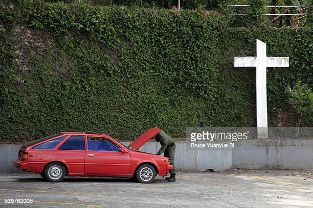 A man fixing his car on street