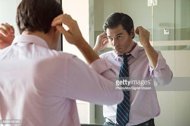 Man fixing his hair in bathroom mirror