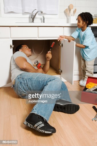 Father And Son Fixing Pipe Under Kitchen Sink Stock Photo | Getty Images