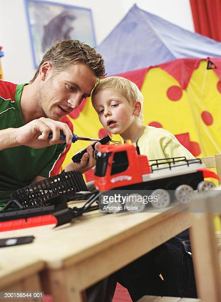 Man fixing toy with screwdriver, boy (2-4) looking on