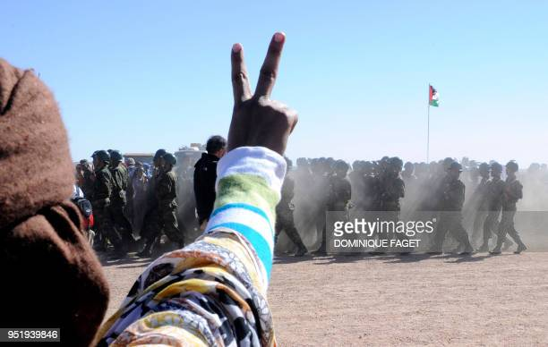 A man flashes a vsign as soldiers from the Proindependence Polisario Front parade during a ceremony marking the 35th anniversary of the proclamation...