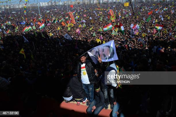 A man flashes the 'V for Victory' sign and waves a flag with a picture of jailed Kurdish rebel leader Abdullah Ocalan as people gather to celebrate...