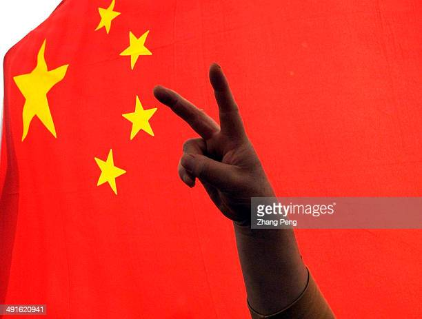 A man flashes the victory sign in front of a China flag as thousands gather at Tian'anmen Square for three minutes of silence to show respect to the...