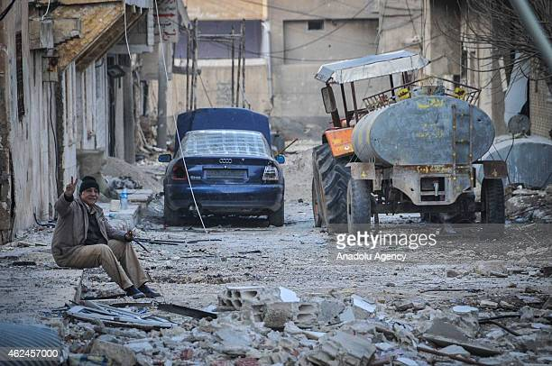 A man flashes victory sign among the wreckage left by fighting on a street in the center of the Syrian town of Kobani on January 28 2015 after it has...