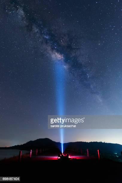 Man, flashlights and the Milky Way , stars light night sky. Long exposure photograph with grain .